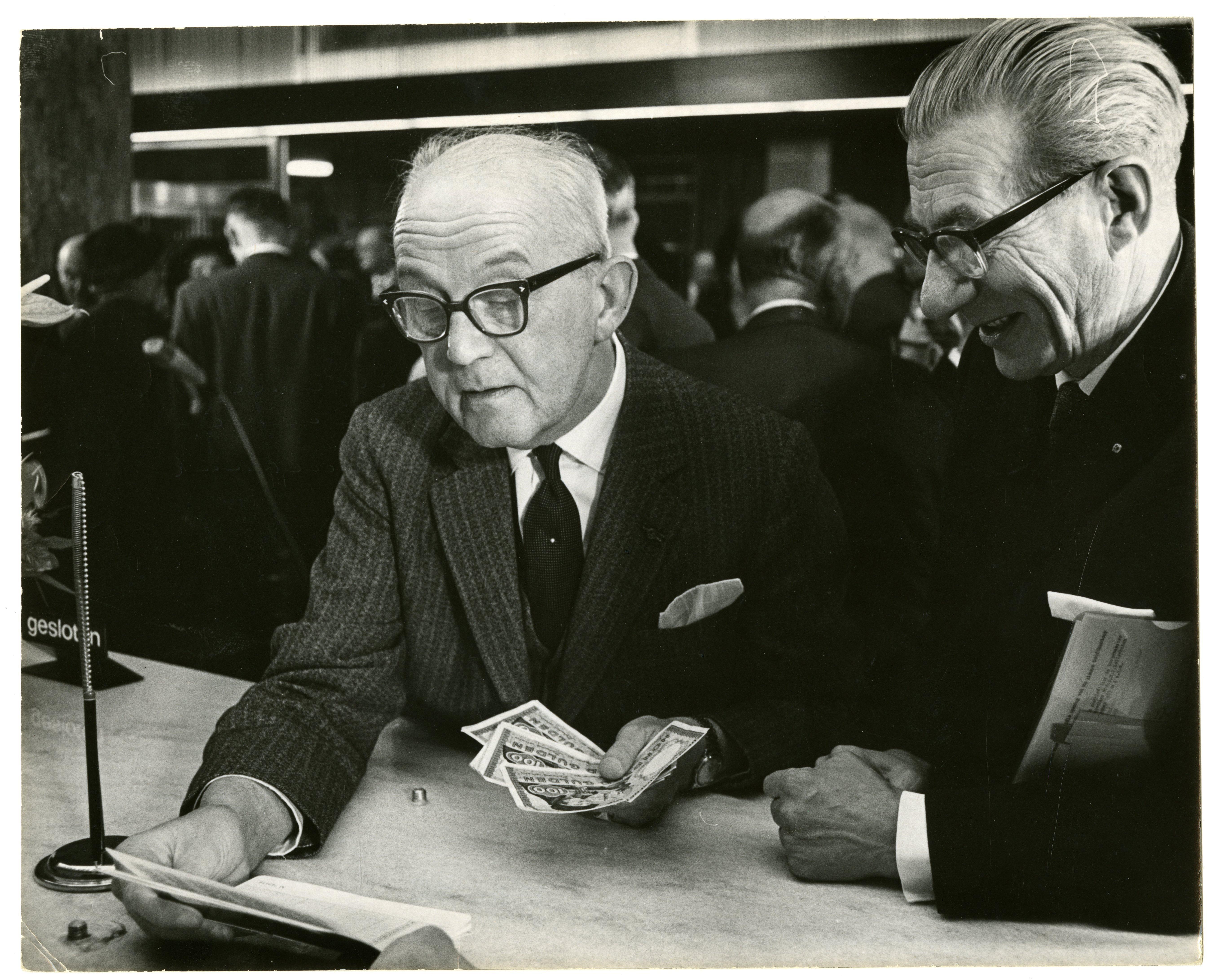 Burgemeester Kolfschoten opende het nieuwe kantoor door geld in te leggen op een spaarbankboekje. Vervaardiger Haagsche Courant, collectie Haags Gemeentearchief.